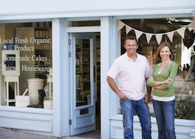 Couples Standing In Front Of Organic Food Store Smiling