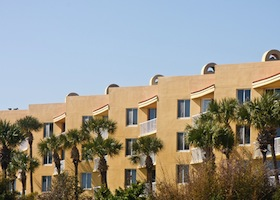 A tropical condo building of yellow stucco